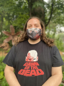 A young man with long, brown hair, standing outdoors wearing a Dawn of the Dead t-shirt
