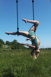 """Aerialist Rachael hangs in a """"French gazelle"""" pose, suspended from two straps. She is outdoors and set against a backdrop of blue sky and green grass."""