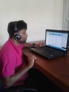 Palitha, wearing a headset, sits at a desk and works on a laptop computer
